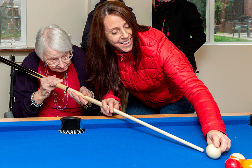 Phyllis Daniels and Lucy Scott playing pool at Tilmore Gardens in Petersfield