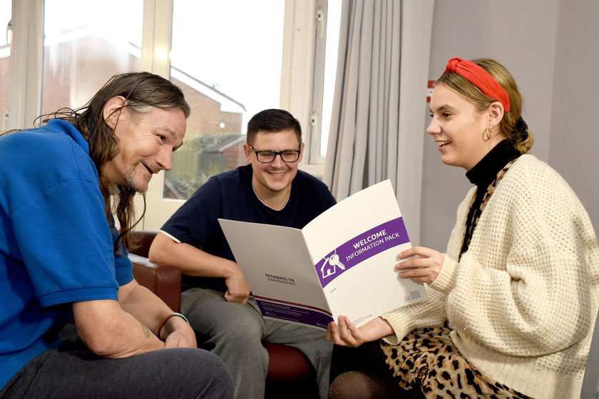 Sanctuary Supported Living residents sat reading their welcome pack.