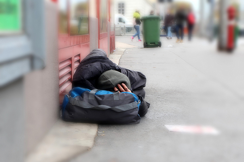 Homeless man lying on a busy street