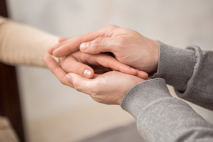 A person supportively holds an outstretched hand.