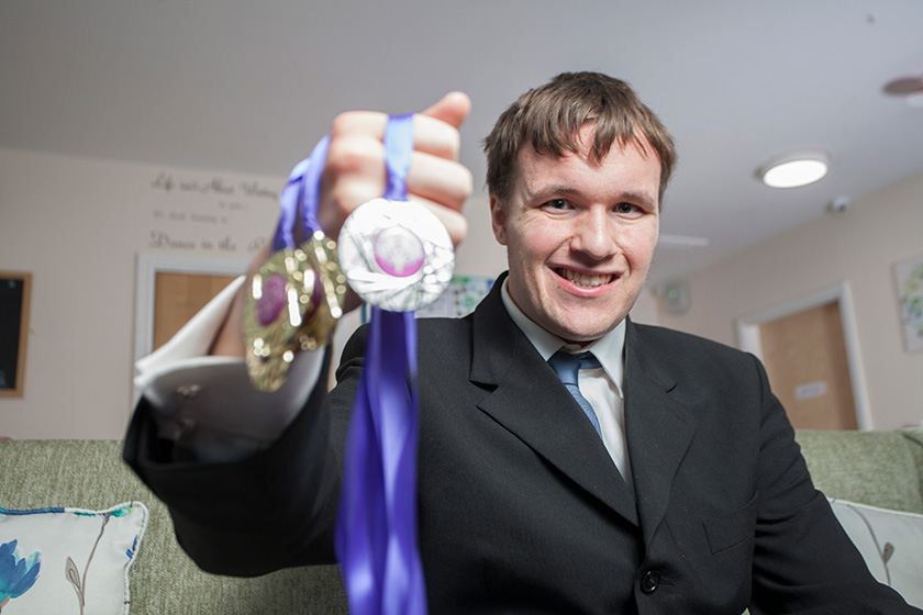 James Noble holding his medals.
