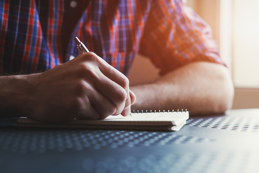 Man writing on a notepad.