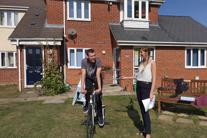 Resident Harry cycles on the excercise bike outdoors with Lauren timing his ride.