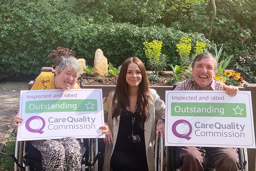 Residents of Hilltop House hold up the Outstanding CQC posters beside the service manager