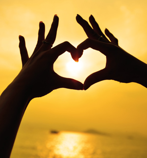 Two hands making a love heart in front of a sunset.