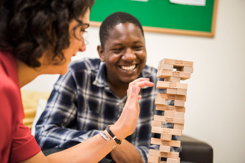 A resident playing Jenga with a staff member.