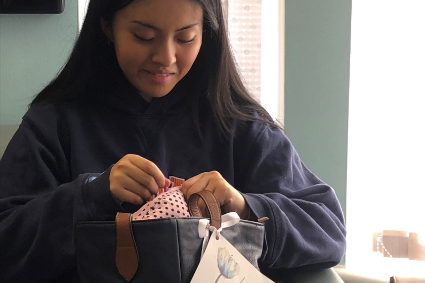 A young woman is excited to receive a free handbag filled with goodies from a local charity.