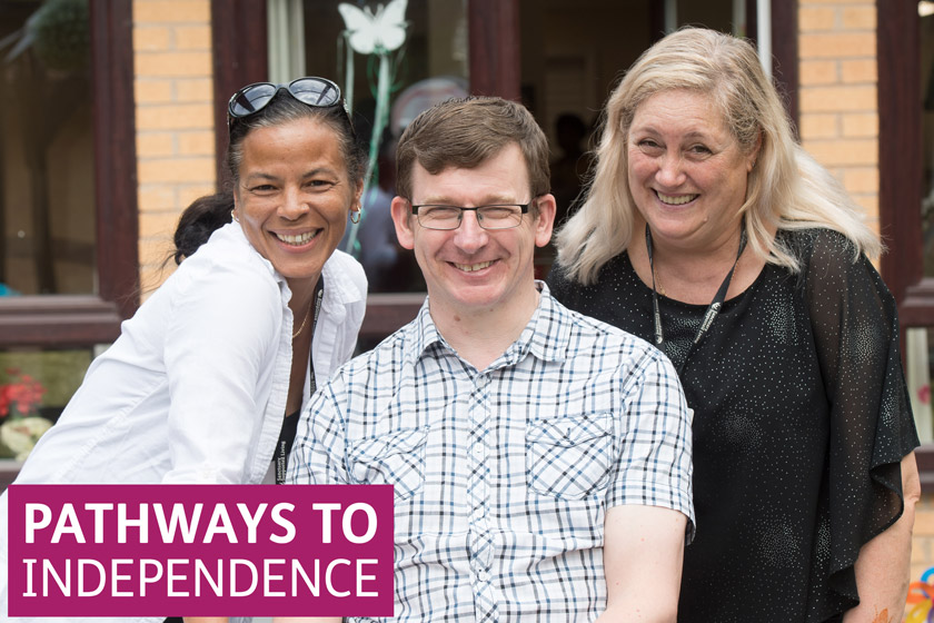 Pathways to independence logo upon a picture of two staff members with a resident
