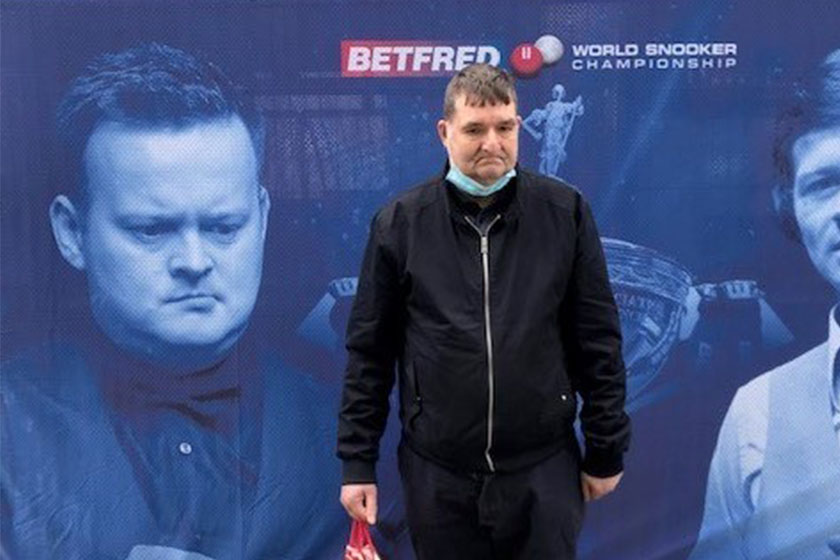 Robert stands in front of a billboard featuring his favourite snooker players