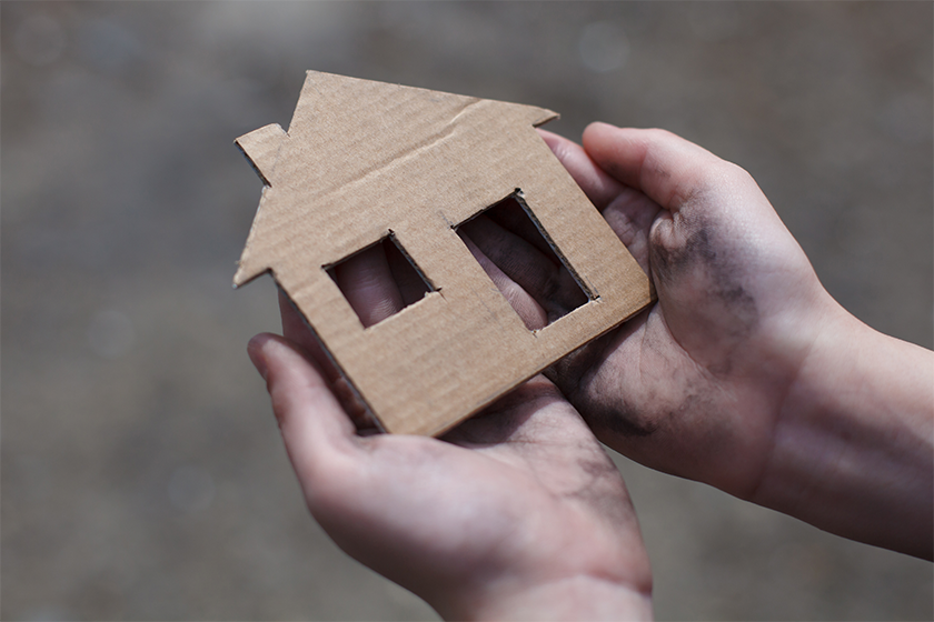 A pair of hands holding a cardboard cut out of a house
