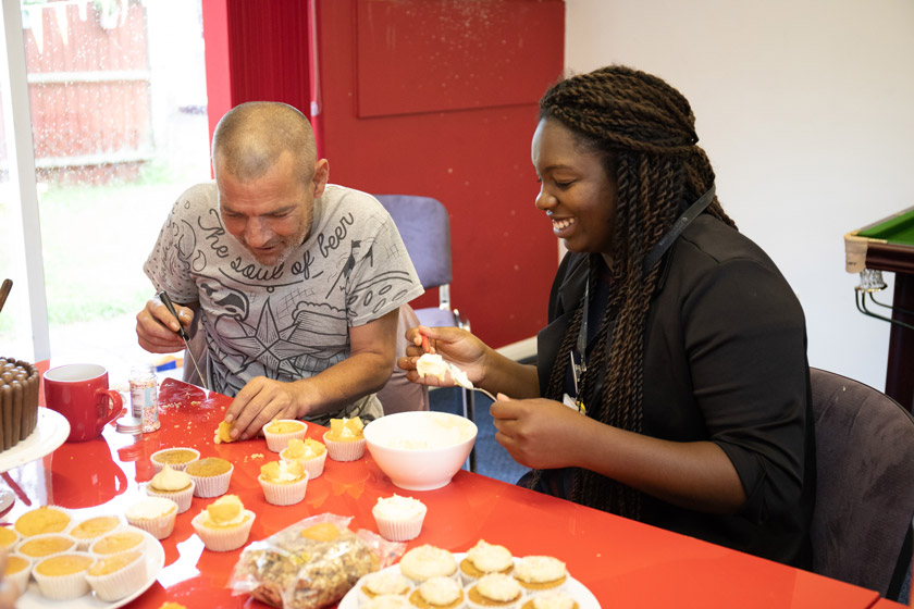 A resident and staff member decorating cakes at Chelmsford Homelessness Supported Housing.