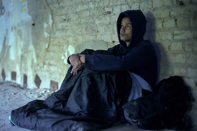 A young man wearing a hoody sits in a sleeping bag against a brick wall
