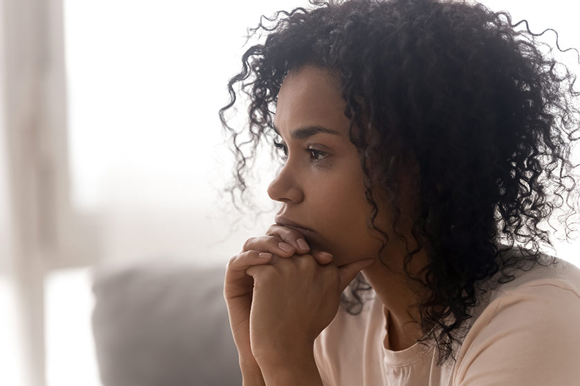A troubled looking woman sits deep in thought