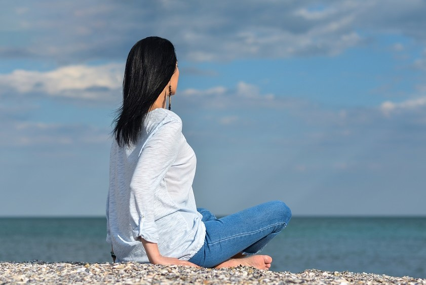 A woman meditates while sitting on a pebbled beach