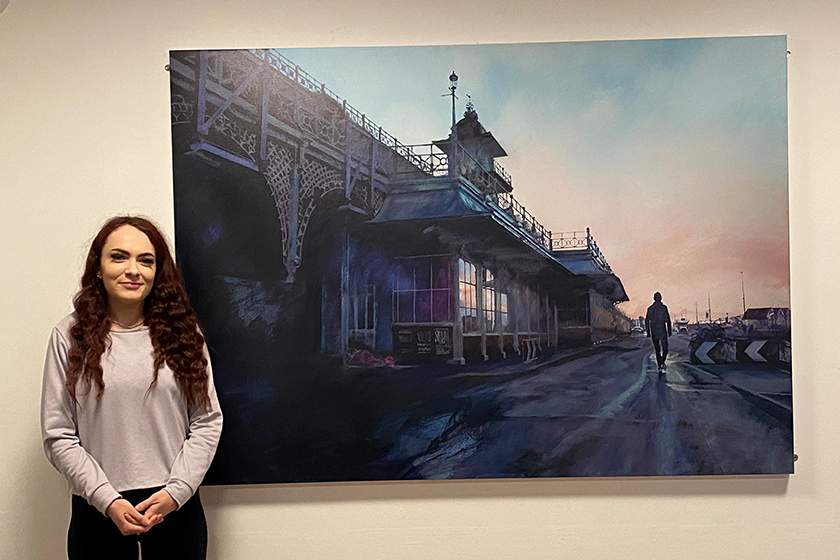 Resident, Jade, stands by a large photograph of Brighton Pier, hanging on a wall