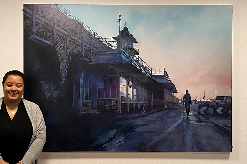 Resident, Leah, stands by a large photograph of Brighton Pier, hanging on a wall