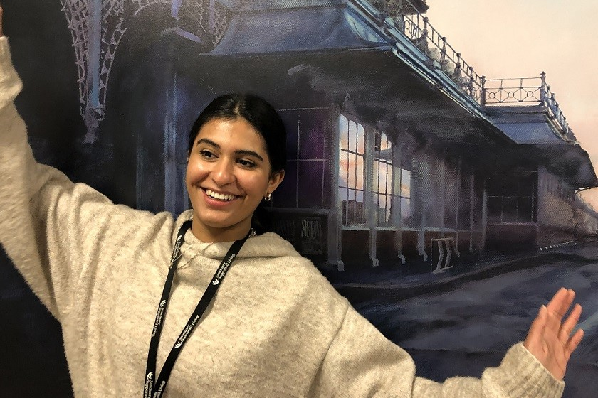 Sahara Henerey, project worker, laughs with open arms on Brighton Pier