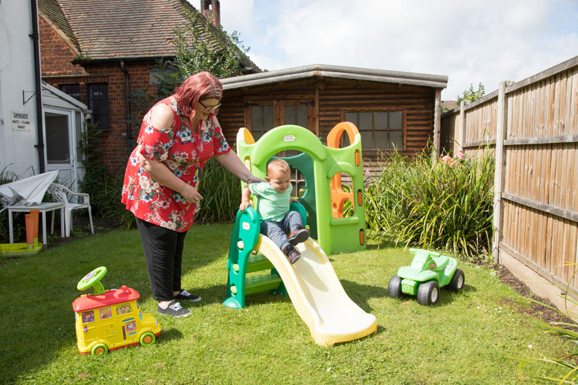 A staff member and young resident in the garden at Thurrock Teenage Parents Supported Housing.