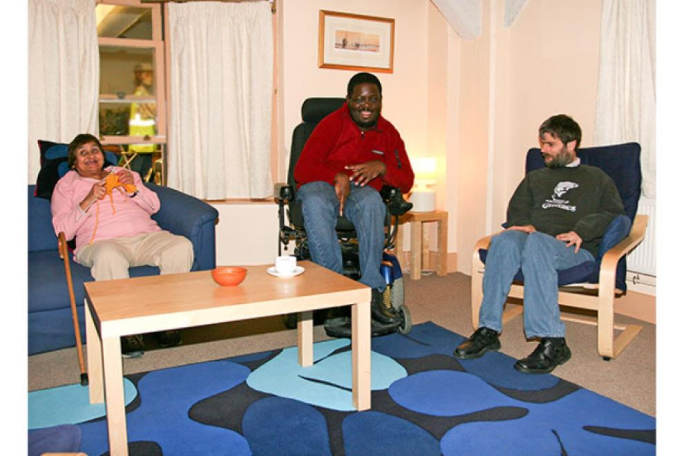 Three residents sat in a communal lounge