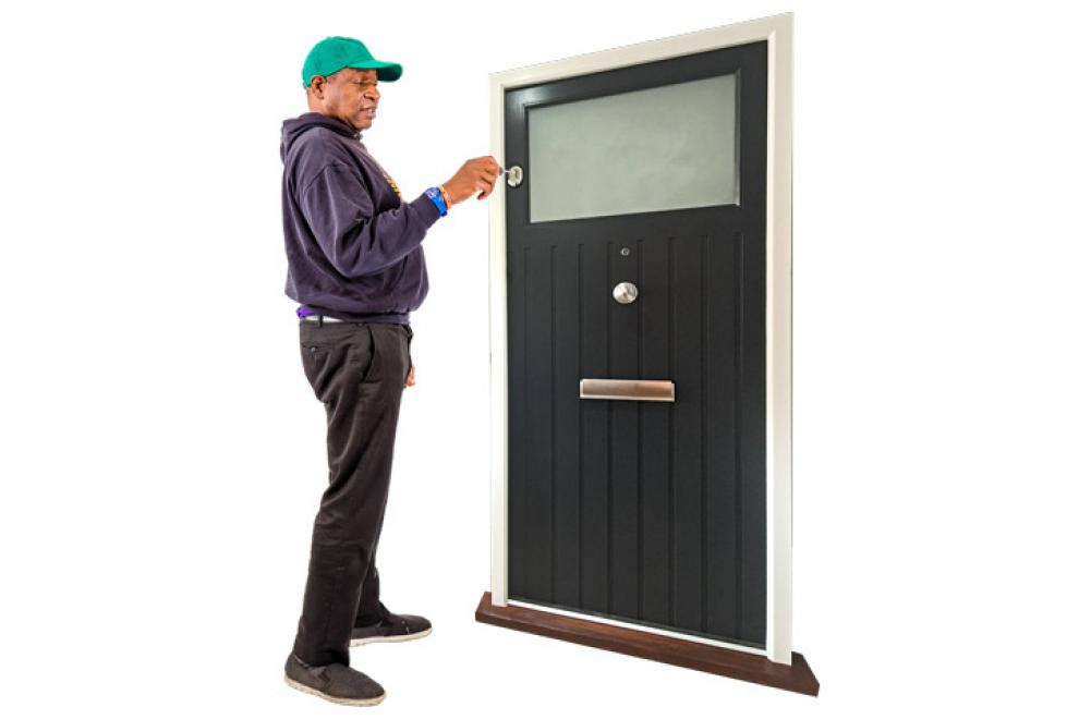 A resident using his own key to open his door.
